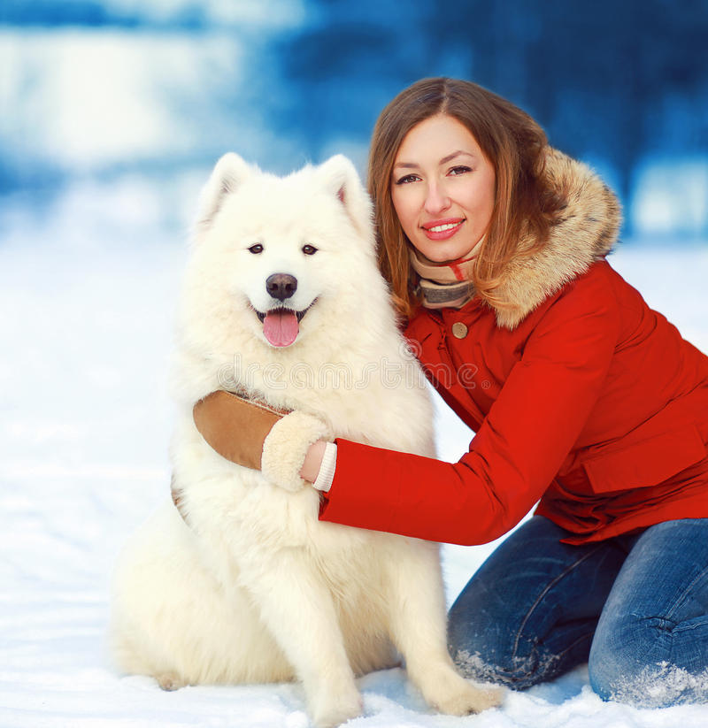 Happy smiling bright woman with Samoyed dog outdoors royalty free stock photo