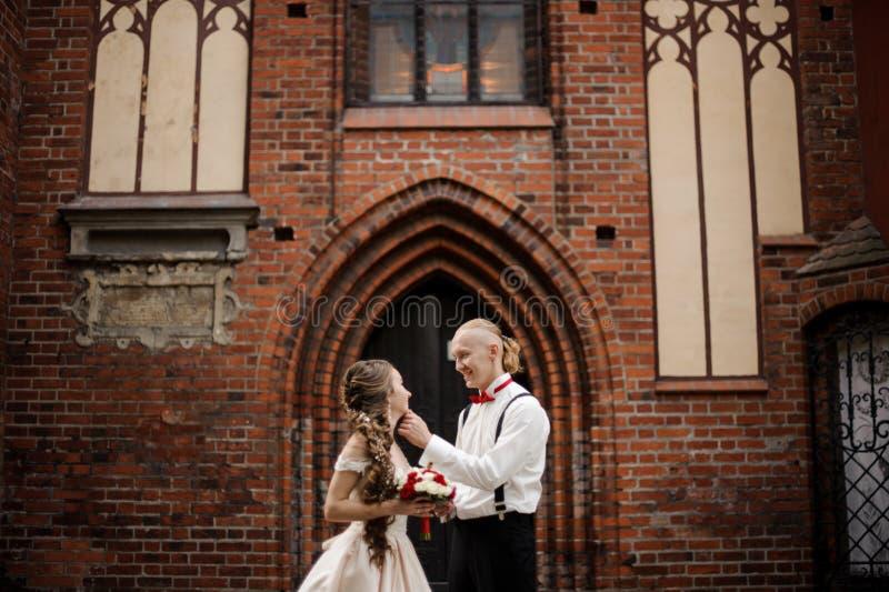 Happy smiling broom touching his beautiful bride cheek stock photos