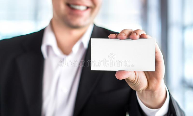 Happy smiling business man holding empty white business card. In modern office building. Free blank copy space stock photos