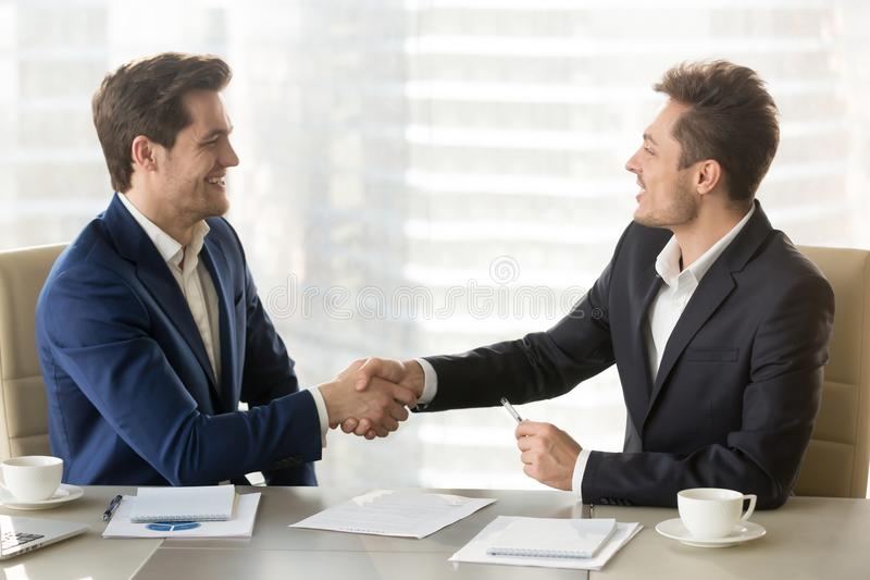 Two businessmen handshaking after good negotiation. Happy smiling business partners shaking hands and congratulating each other after singing contract stock photo