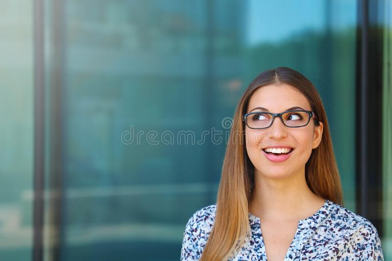 Happy smiling business woman with glasses looks up copy space area stock image