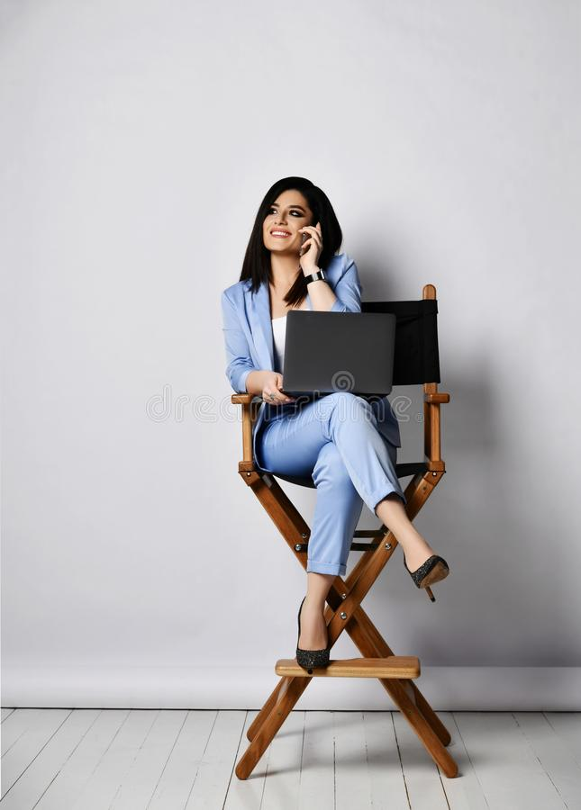 Smiling business woman in official suit and high-heeled shoes sitting with laptop on armchair and chatting by cell phone stock photography