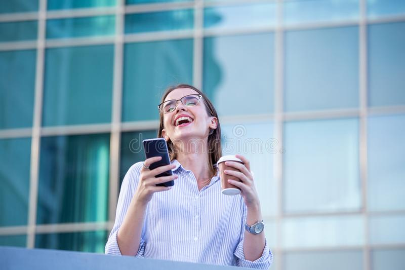 Happy smiling business woman talking on mobile smartphone and drinking coffee from disposable paper cup in the street with office royalty free stock images