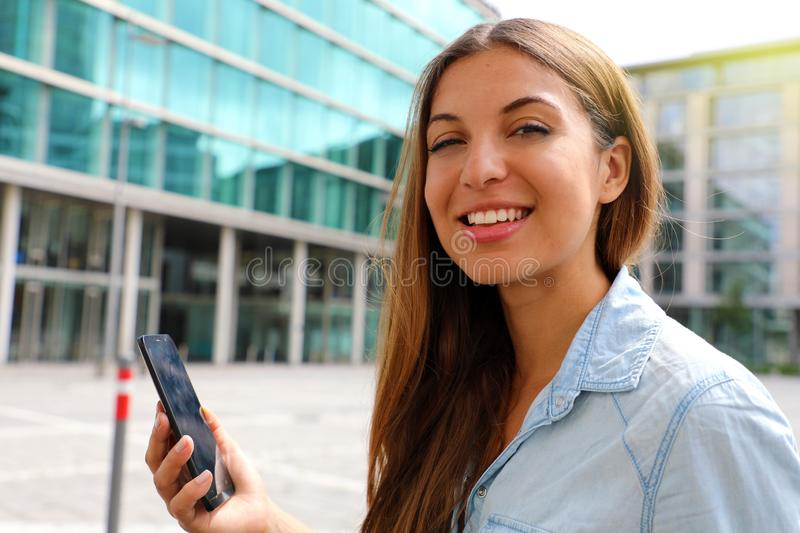 Happy smiling business woman using her smart phone sitting outdoor royalty free stock image