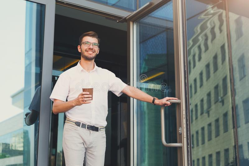 Happy smiling businessman with coffee leaving the building stock photography