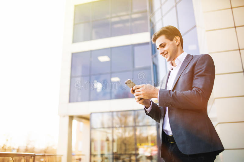 Happy smiling businessman wearing suit and using modern smartphone near office at early morning royalty free stock photos