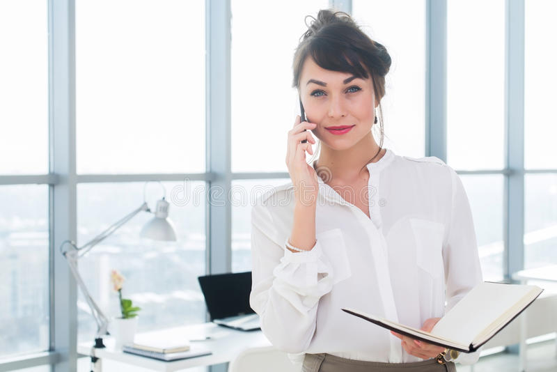 Happy smiling businesswoman having a business call, discussing meetings, planning her work day, using smartphone. royalty free stock photography