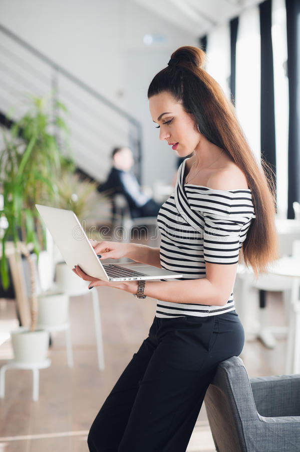 Happy smiling businesswoman leaning on the office desk and using pc tablet. stock photography