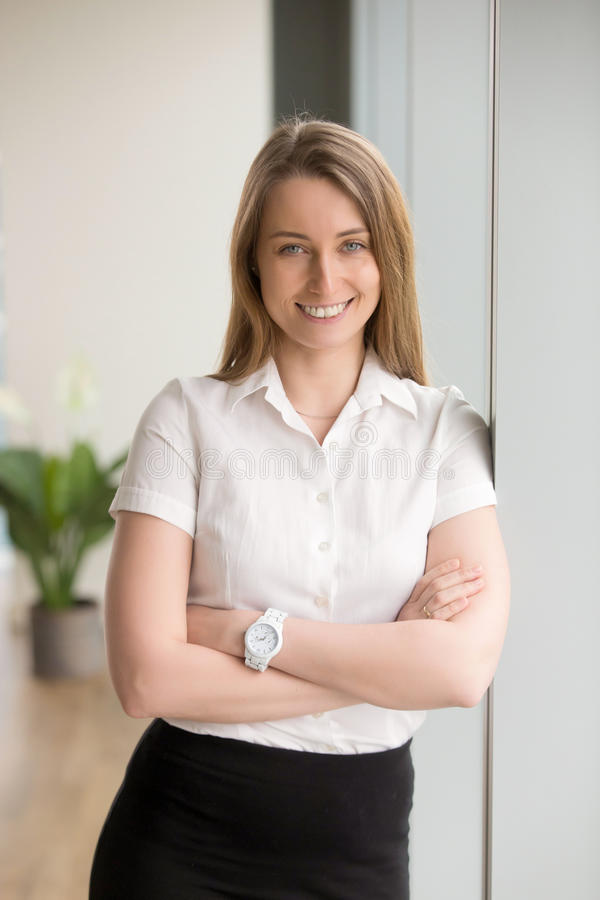 Happy smiling businesswoman looking at camera with arms crossed,. Attractive positive entrepreneur posing in office, talented skilled manager having successful royalty free stock image