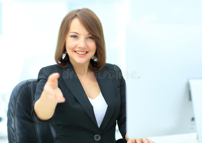 Happy smiling businesswoman in suit giving hand for handshake. Invitation concept. Elegant young business woman welcoming guests royalty free stock image