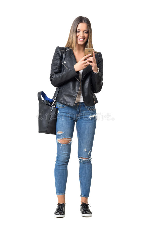 Happy smiling casual street style girl typing on the cellphone. Full body length portrait isolated over white background stock image