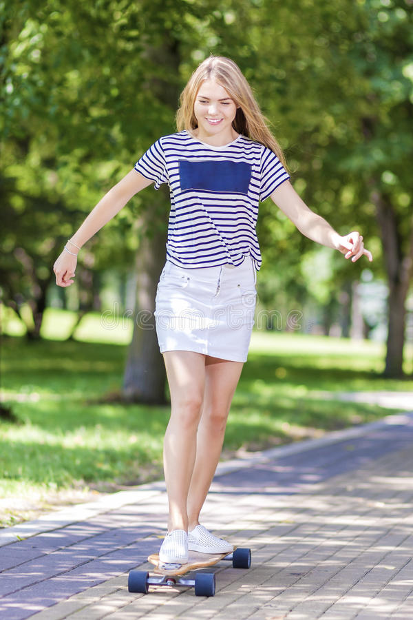 Happy Smiling Caucasian Blond Teenager Girl Skating on Longboard Outdoors royalty free stock image