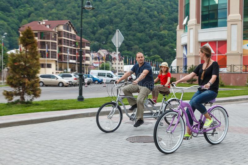 Happy smiling Caucasian family of father, mother and daughter have outdoor bicycle ride at summer on hotel buildings background. stock photos