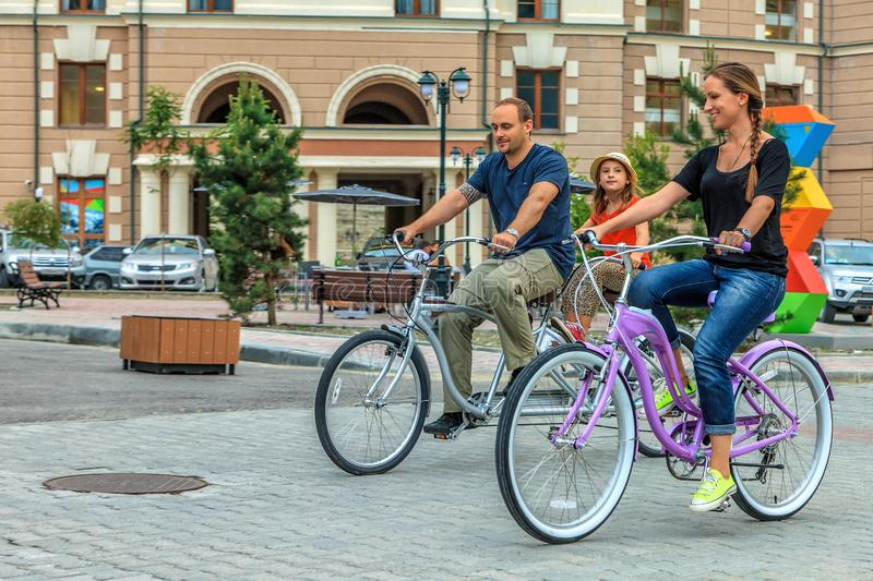Happy smiling Caucasian family of father, mother and daughter ride bicycles outdoors in the street at resort stock photos