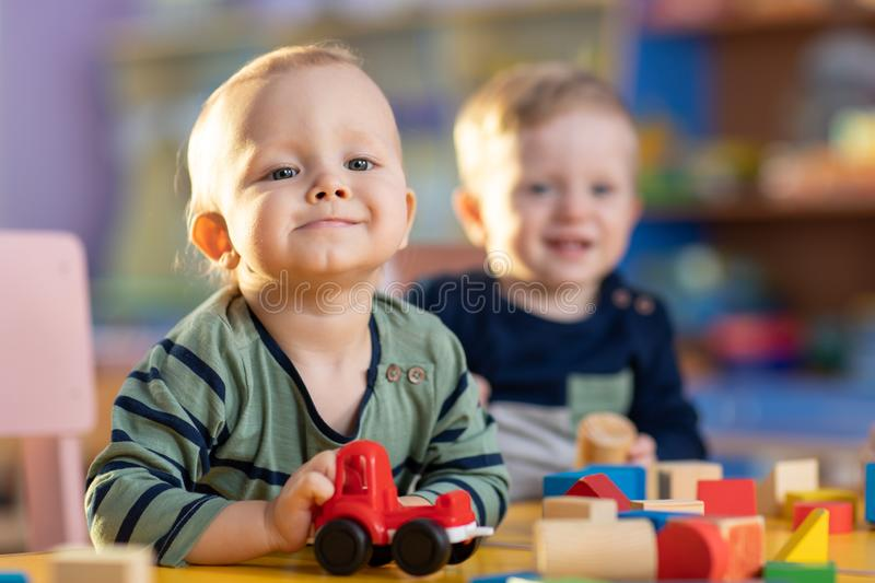 Happy smiling caucasian kids are playing with educational toys in nursery stock photography