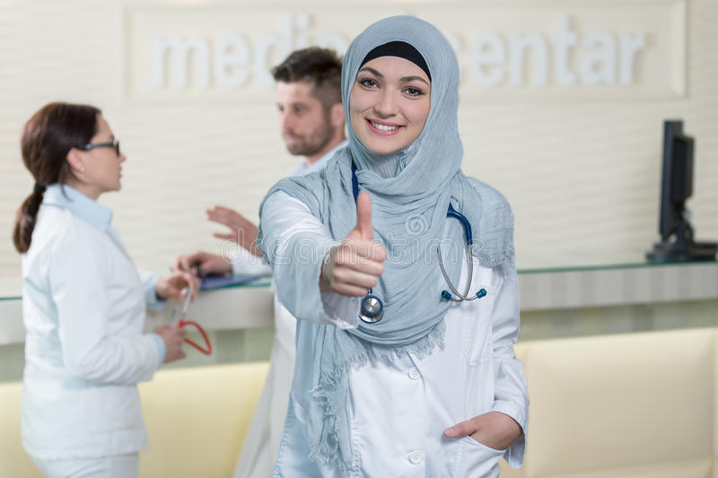 Happy smiling cheerful female muslim doctor with thumbs up gesture royalty free stock photo