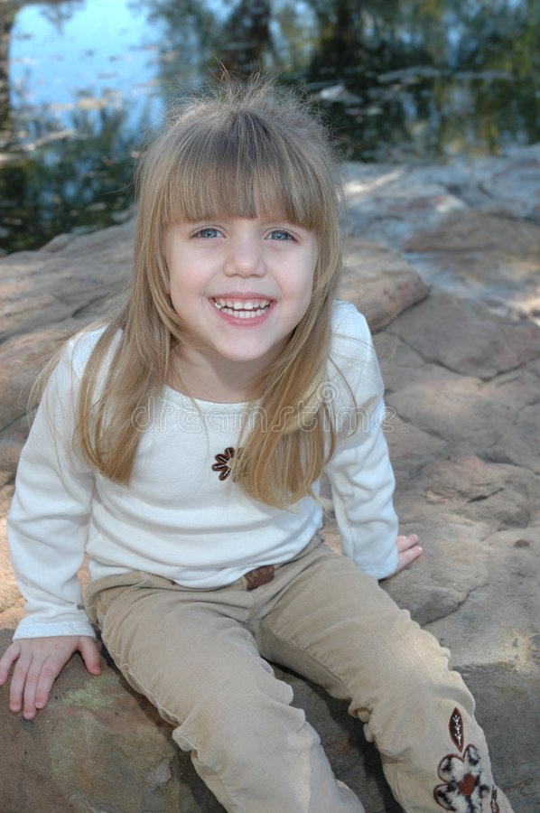 Happy Smiling child. A beautiful little blond girl with blue eyes smiles and laughs as she sits on a rock in a nature area of a park royalty free stock images