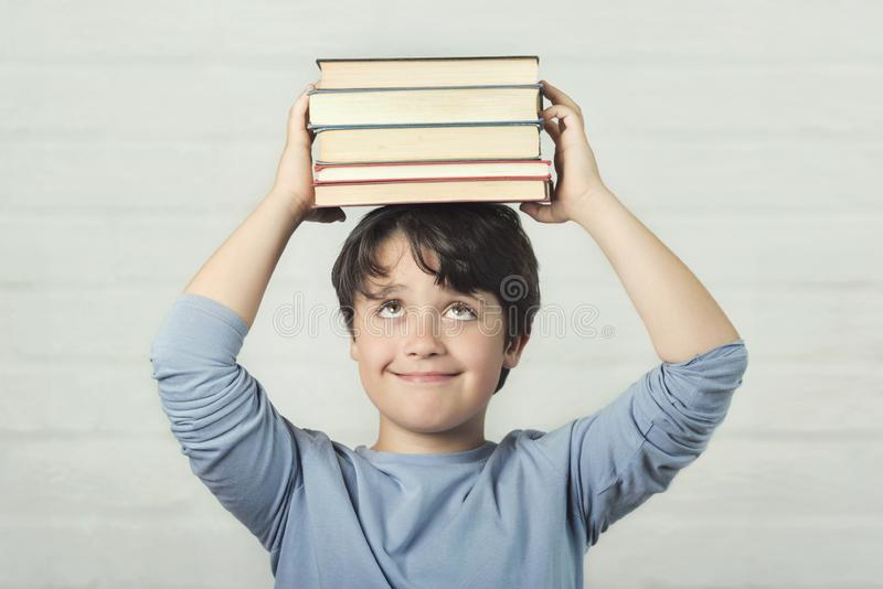 Happy and smiling child with books on head stock photography