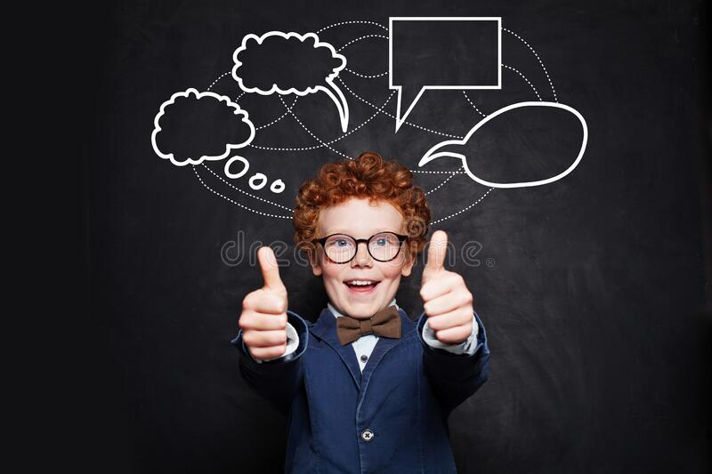 Happy smiling child with empty speech bubbles on chalkboard background royalty free stock image