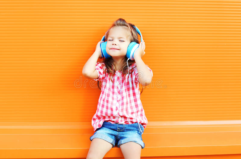 Happy smiling child enjoys listens to music in headphones over colorful orange. Background stock images