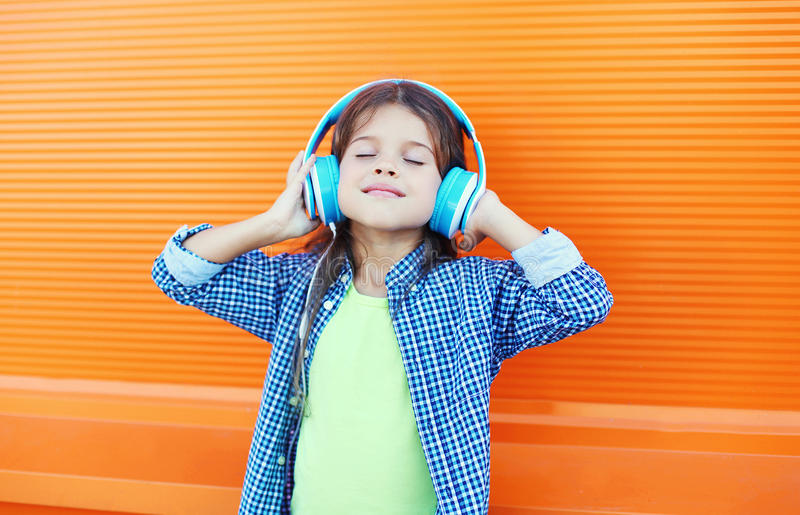 Happy smiling child enjoys listens to music in headphones over colorful orange. Background royalty free stock photography