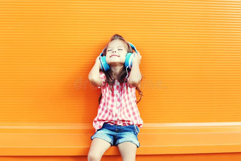 Happy smiling child enjoys listens to music in headphones over orange. Background royalty free stock photo