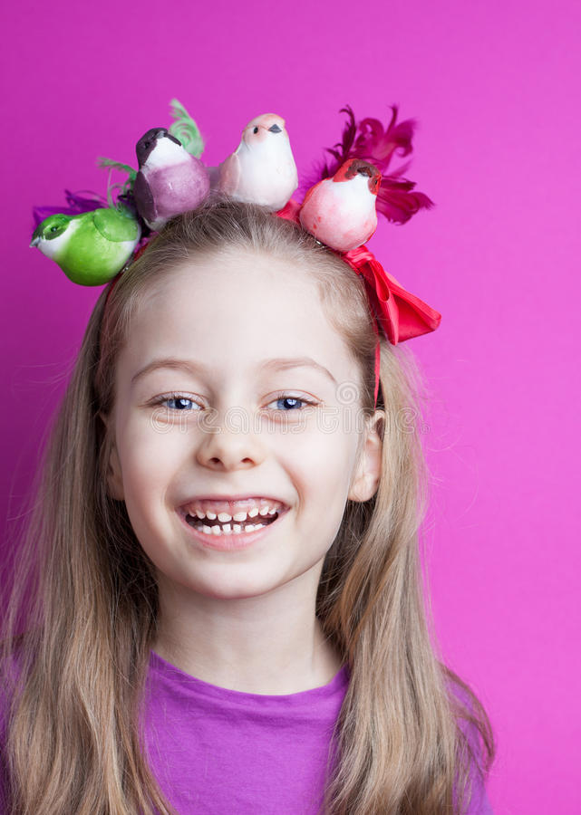 Happy smiling child girl with colorful birds on head. Happy smiling five years old blond caucasian child girl with colorful birds on head - pastel purple royalty free stock images