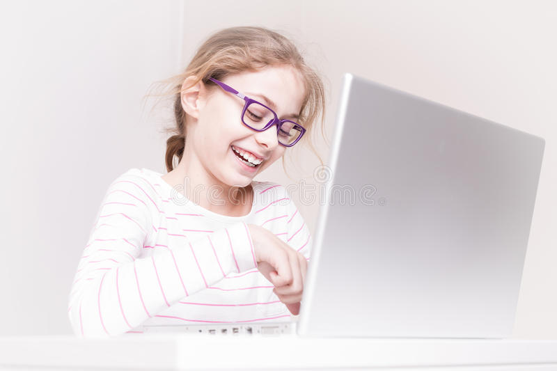 Happy smiling child girl kid using laptop computer. Eight years old, caucasian, happy smiling blond child girl kid using laptop computer. Childhood and modern royalty free stock images