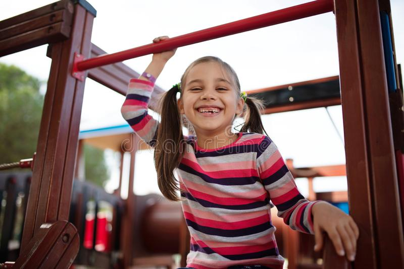 Happy Smiling Child Girl Playing on the Playground In Park. Happy Smiling Child Girl Playing on the Playground Outdoors In the Park stock photos