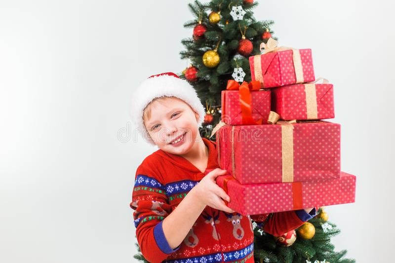 Happy smiling child holding pile of present boxes royalty free stock image