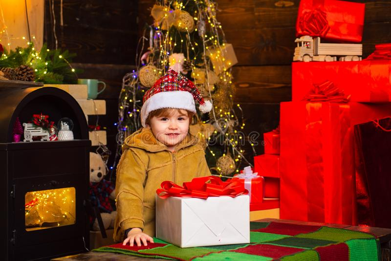 Happy smiling child with new year gift. Merry Christmas and Happy Holiday. Girl kid santa hat with present counting time stock photos
