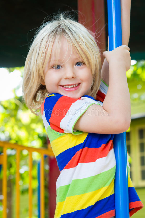 Happy, smiling child playing in a play ground. Happy, smiling child playing on a pole in a play ground outside royalty free stock photos
