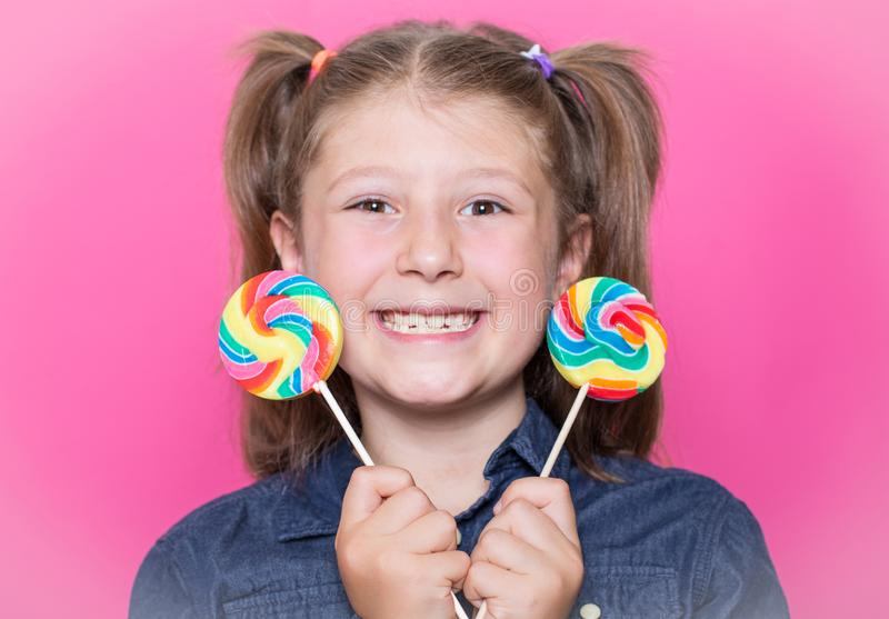 Happy smiling child with sweet lollipop having fun over colorful pink background royalty free stock images