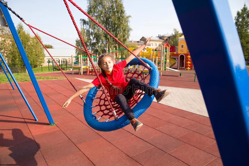 Happy smiling child swinging on a swing with closed eyes and arms outstretched at playground stock photos