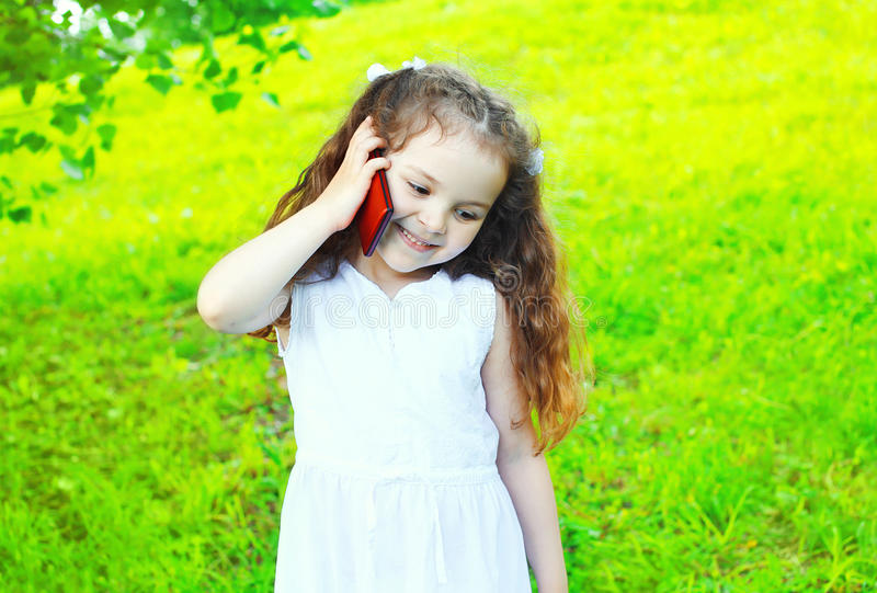 Happy smiling child talking on smartphone in summer royalty free stock photography