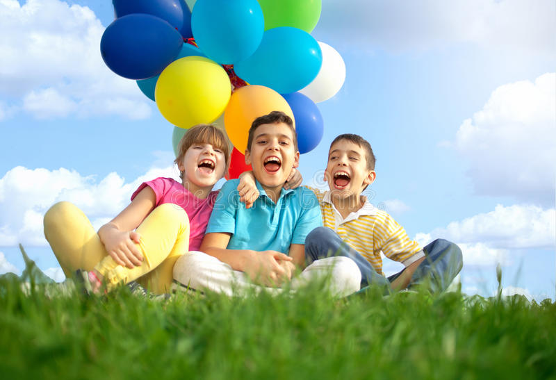 Happy smiling children playing with colorfull balloons. Happy smiling group of kids with balloons on a green meadow stock photography