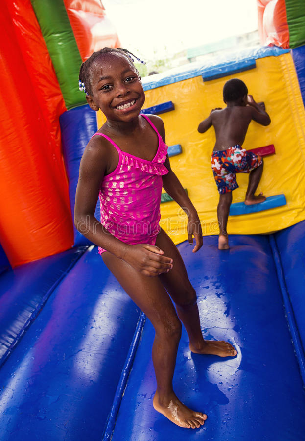Happy smiling children playing on an inflatable bounce house. Cute smiling young children playing on an inflatable bounce house outdoors. Diverse children royalty free stock photo