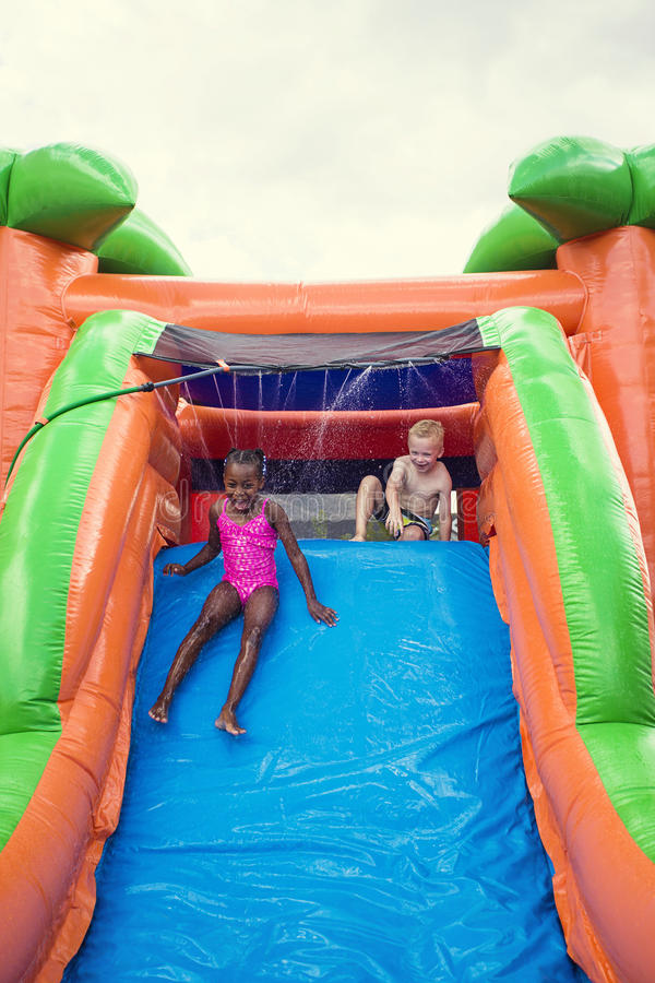 Happy smiling children playing on an inflatable slide bounce house. Cute smiling young children playing on an inflatable slide bounce house outdoors. Diverse stock image