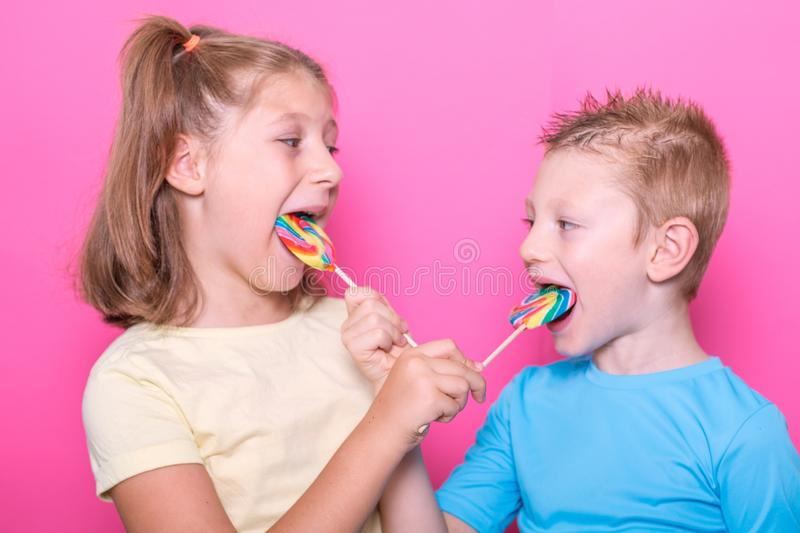 Happy smiling children with sweet lollipop having fun over colorful pink background stock photos