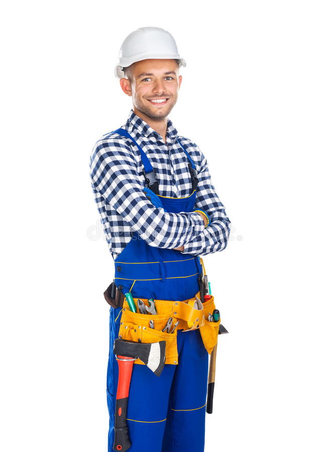 Happy smiling construction worker in uniform and tool belt with. Crossed arms isolated on white background royalty free stock image