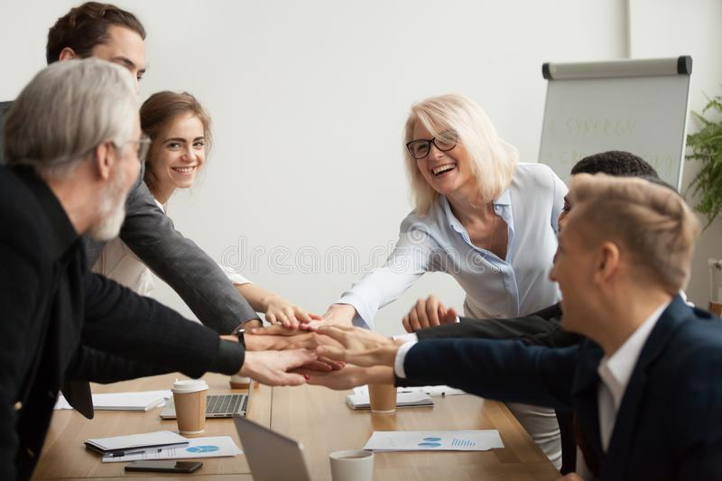 Happy smiling corporate team join hands together at group meetin. Happy smiling corporate team of senior executives and young employees join hands together at royalty free stock image