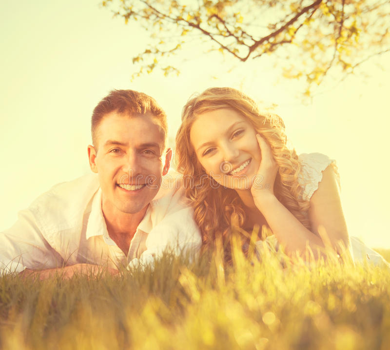 Happy smiling couple lying on grass. Happy smiling couple together relaxing on grass in a park royalty free stock photography