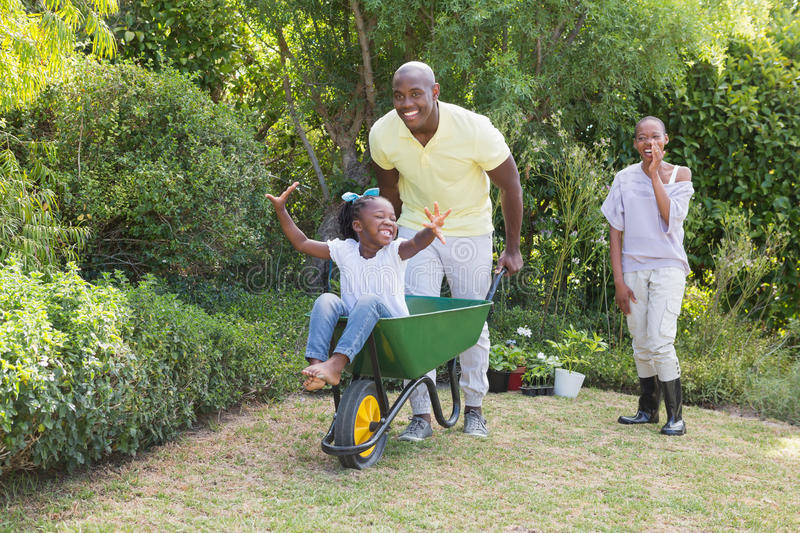 Happy smiling couple playing with wheelbarrow and their daughter royalty free stock photography