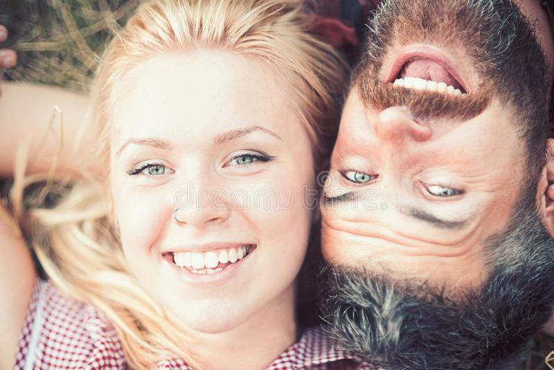 Happy smiling couple relaxing on green grass in park. Young couple lying on grass outdoor stock photo
