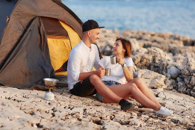 Happy smiling couple sitting face to face at rocky beach on near tent. royalty free stock images