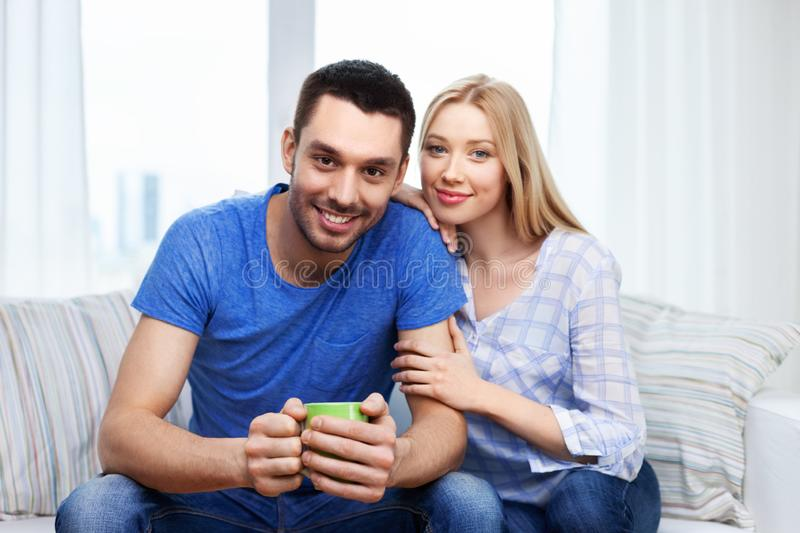 Happy smiling couple sitting on sofa at home royalty free stock images