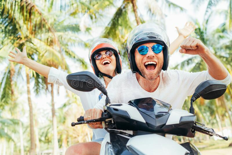 Happy smiling couple travelers riding motorbike scooter in safety helmets during tropical vacation under palm trees on Ko Samui royalty free stock image