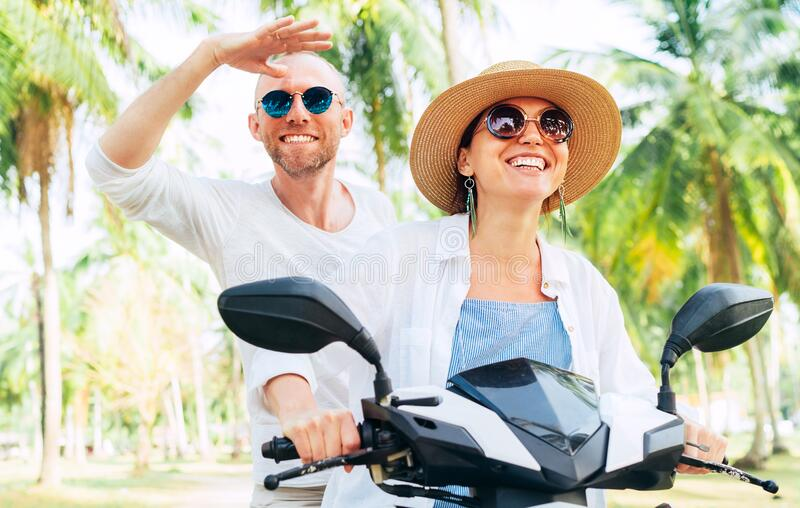 Happy smiling couple travelers riding motorbike scooter under palm trees. Thailand tropical vacation concept image stock image