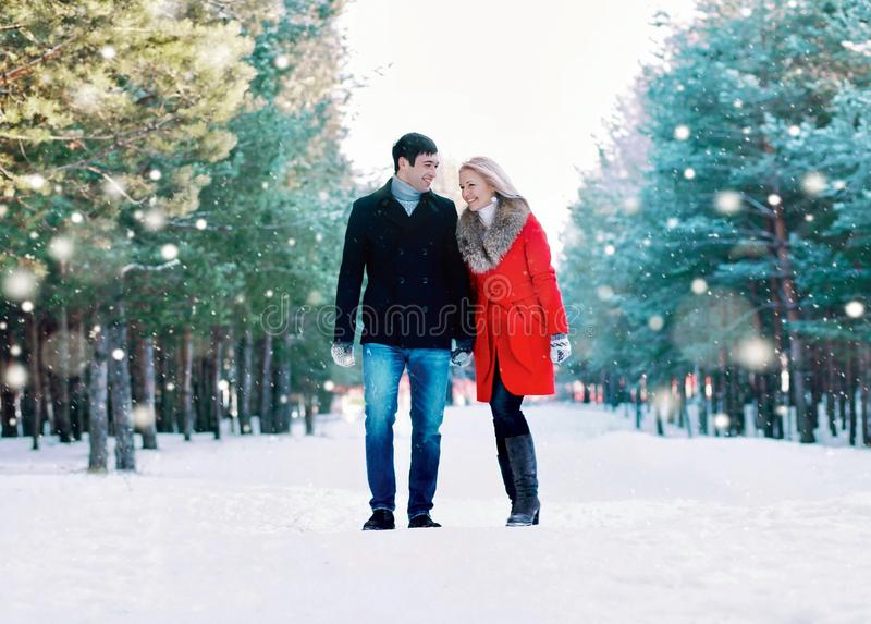 Happy smiling couple walking together, having fun in winter forest royalty free stock images