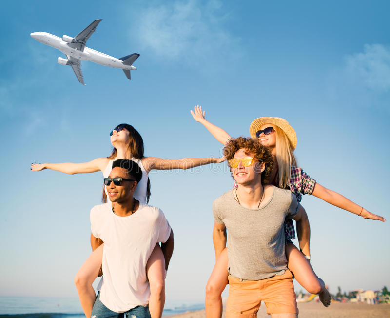 Happy smiling couples playing at the beach with aircraft in the sky stock photo